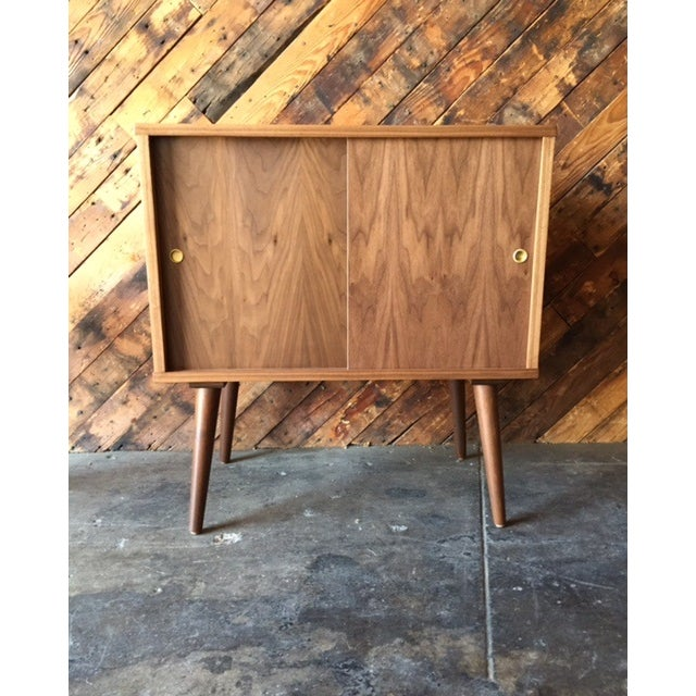 Newly made, Mid-Century-style custom record or bar cabinet. Crafted of walnut, this piece features solid walnut legs as...