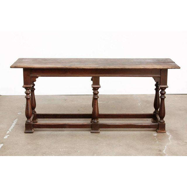 Rustic 19th century English walnut refectory table or console table. Features a plank top made in the William and Mary...