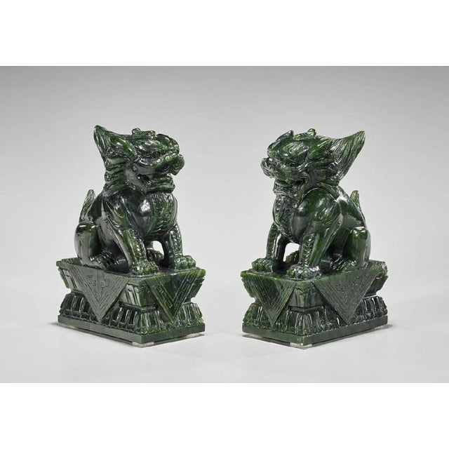 "Pair of Chinese carved spinach jade lions; each seated upon a rectangular double lotus pedestal; measures: H 7 3/4"" (each,..."
