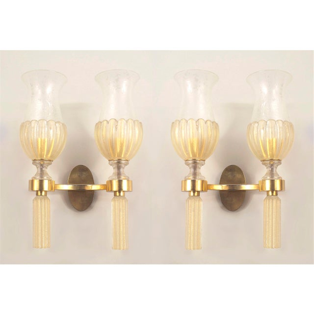 Pair of Italian Venetian Murano 1940s gold dusted glass wall sconces supported by a gilt bronze two arm frame holding...