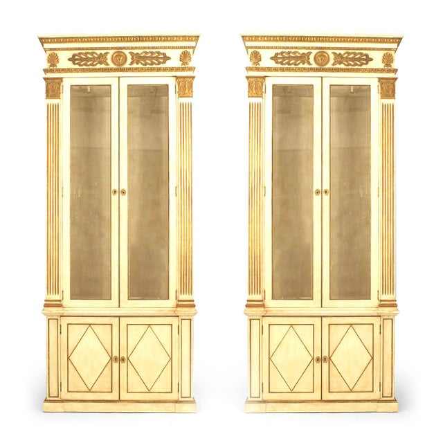 Pair of French Regence style grey painted and gilt trimmed bookcase cabinets with two glass front doors with gilt pilaster...