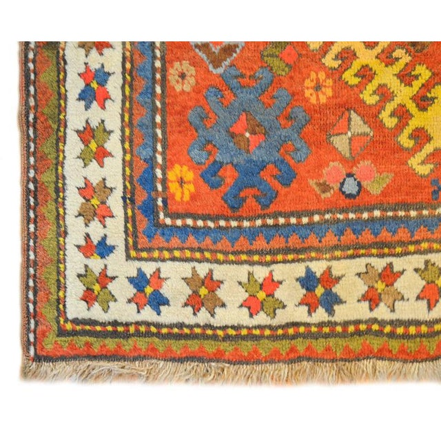 An unbelievable early 20th century Persian Kazak rug with two large geometric medallions, one yellow and one blue, with...