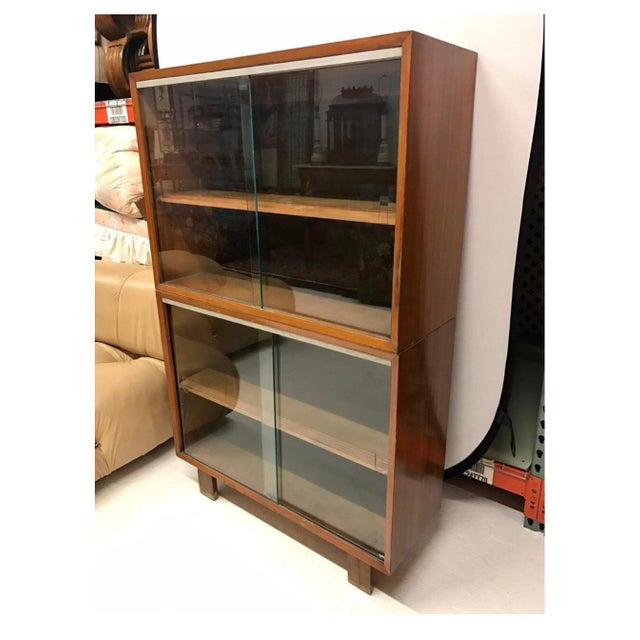 George Nelson walnut bookcase with sliding glass doors on top and bottom. Piece comes with top and bottom for ease of...