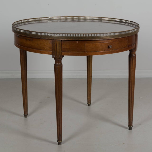 A 19th century Louis XVI style bouillotte table made of mahogany with fluted legs ending in brass sabots. Original grey...