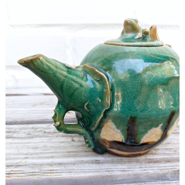 Adorable little frog adorns the lid of this handmade teapot. Leaves and vines complete the made by fairies look.