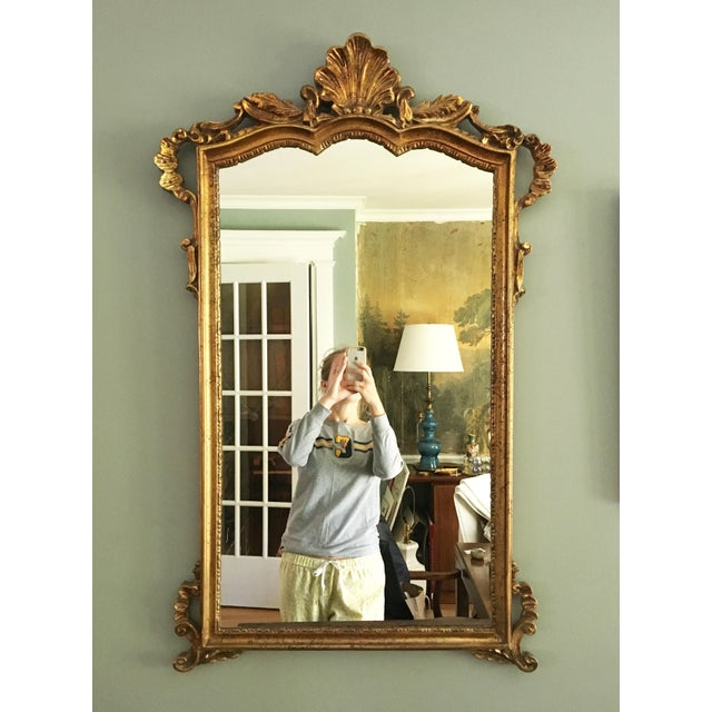 Vintage Rococo style gilt mirror. The mirror is a composite material and is gilded to resemble a gilt wood piece. It has...