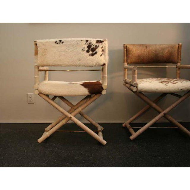 Pair of great directors chairs in cerused faux bamboo with brass detailing. Original cowhide upholstery. Excellent quality.