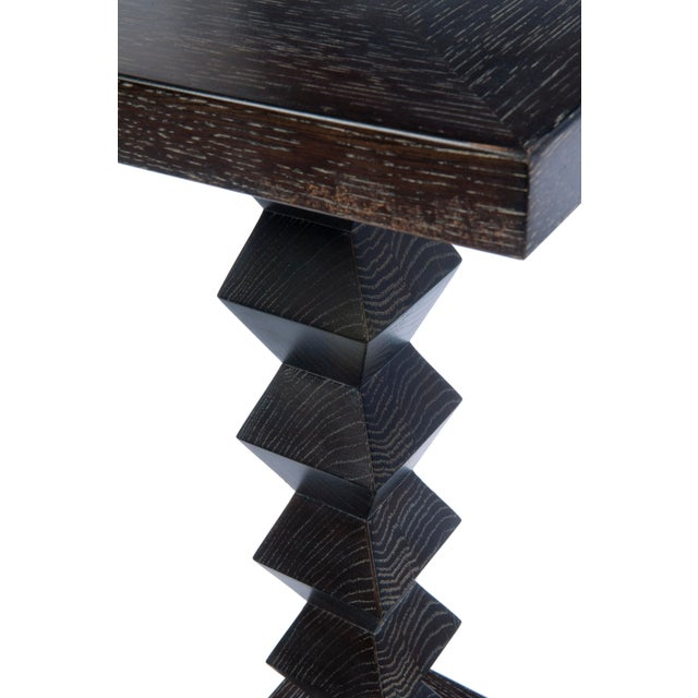 A solid wood table by Donghia features a zig zag column design and plinth base, top is a concentric square inlay design....