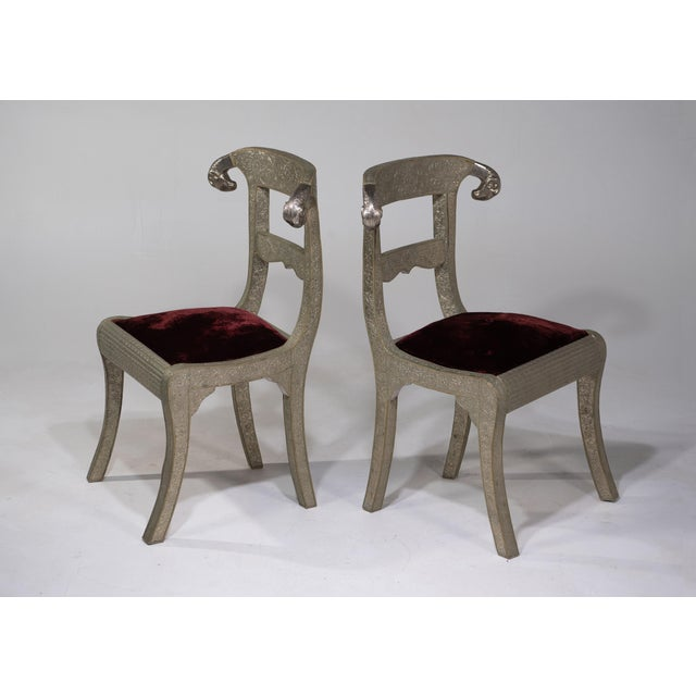 A very glam pair of vintage Anglo-Indian dowry side chairs with fabulous ram's heads and wooden frames clad in...