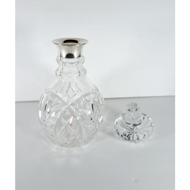 A cut crystal decanter with sterling silver top rim made by John Grinsell & Sons, Birmingham, England. Sold by R&W Sorley...