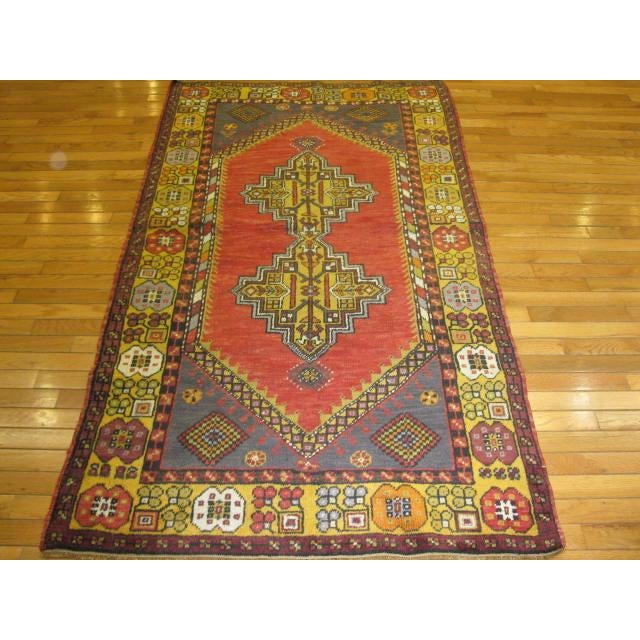 This is a small vintage hand knotted rug with a tribal design . It is made with wool and natural dyes. The rug measures 3'...