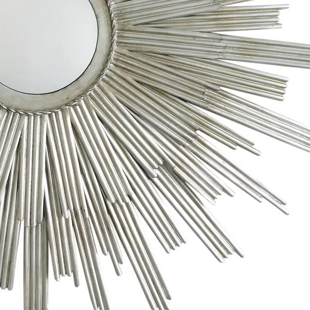 Round sunburst inspired wall mirror features double layer of vertical iron rays in a silver finish.