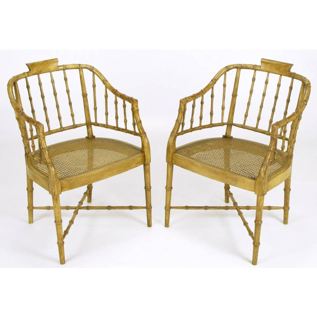 Pair of carved wood bamboo-form arm chairs with an antiqued nutmeg toned glaze. X-stretcher leg supports with woven cane...