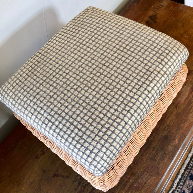 Natural wicker footstool with pale green check upholstery.