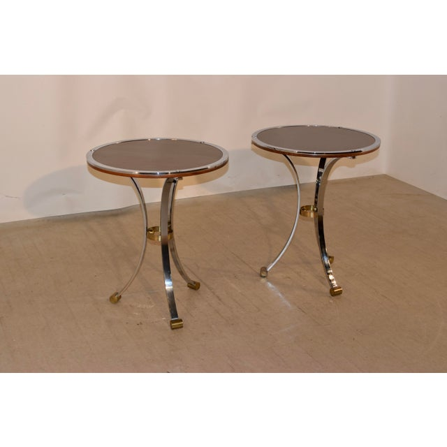Pair of Mid-Century modern side tables from England with mahogany tops, banded in chrome. They are supported on chrome...
