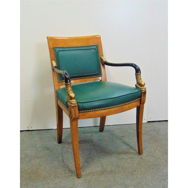 French Empire style arm chair, Maple frame with ebonized and gilt carved dolphin arms, green leather seat and back.