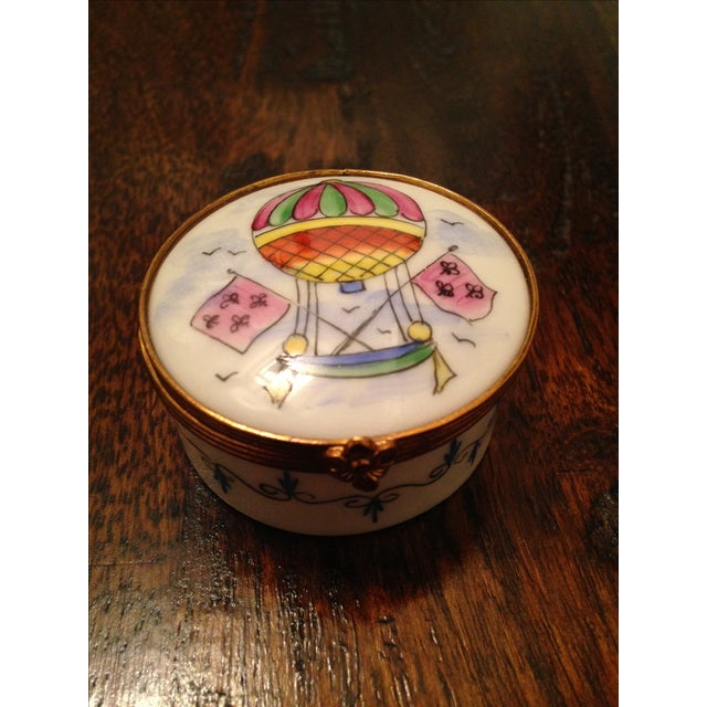 Porcelain trinket box featuring a hand-painted hot air balloon motif. The clasp/hinge is a flower. From Limoges, France.