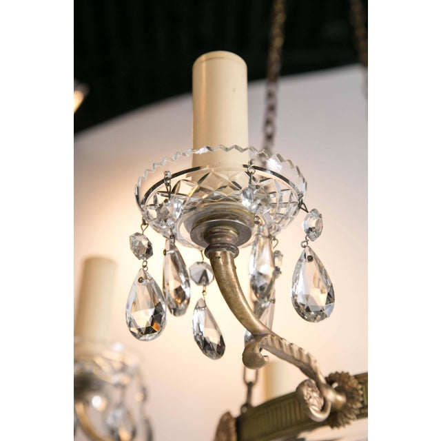A circa 1930 French gilt bronze chandelier with cut crystal inset.