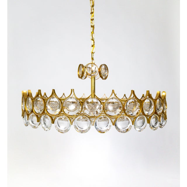An elegant chandelier filled with dangling and strung, optical lens crystals in a gold armature forming a streamlined,...