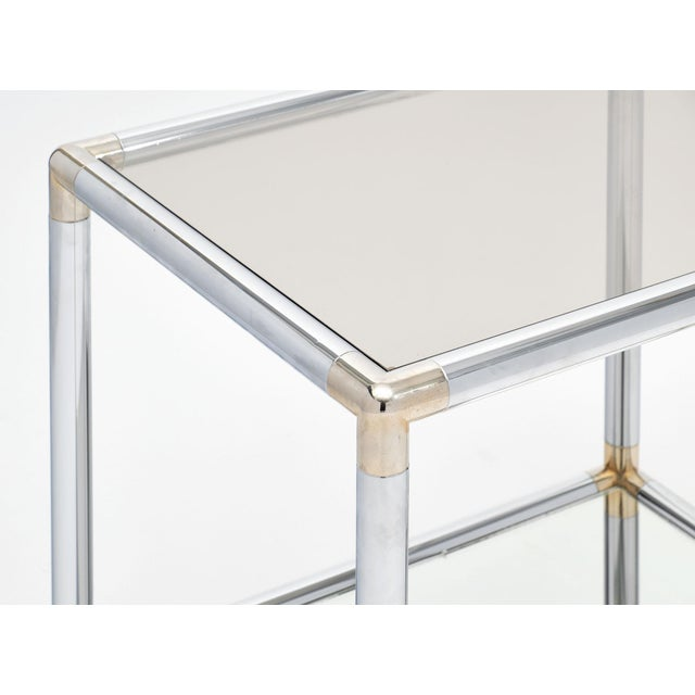 French modernist side table made of chrome and brass. We love the contrast of the metal and the mirrored bottom shelf. The...