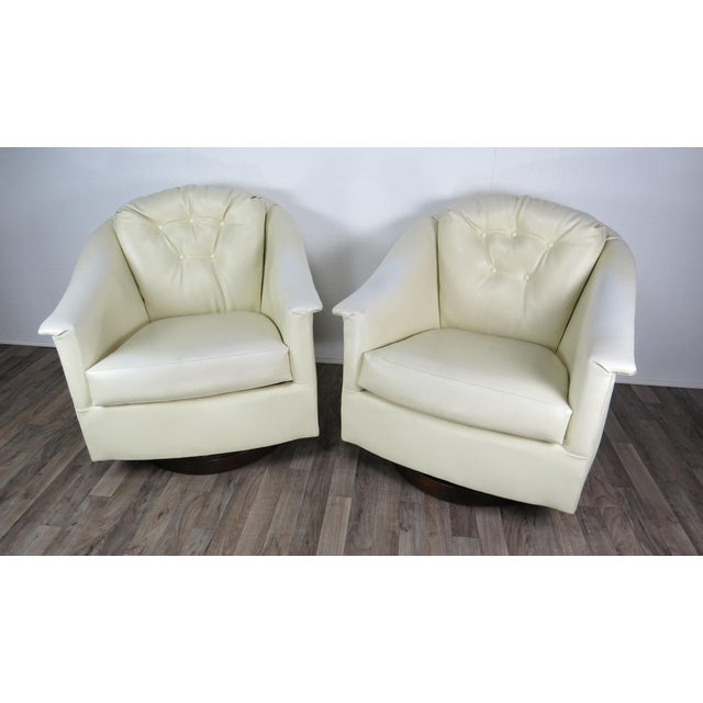 Stunning pair of large white vinyl swivel chairs with iconic flaired arms attributed to Jorgen Kastholm. Button tufted...