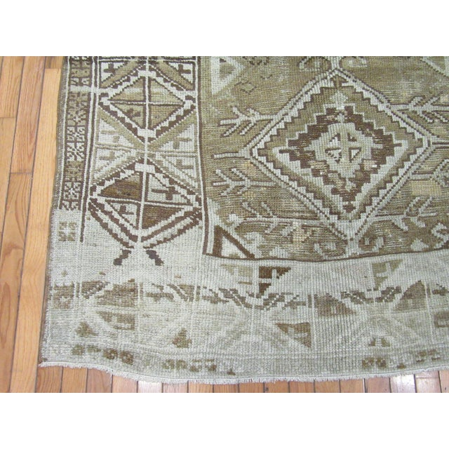 This is a wide and long hand knotted vintage Turkish Anatolian rug. It is made with wool dyed in primary colors. The rug...