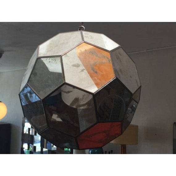 This is a very unique mid-century modern hanging light fixture. It has 32 hexagon mirrors over the entirety of it, all...
