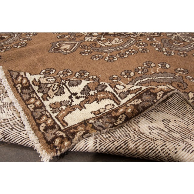 A hand-knotted Mahal rug with a floral medallion design on a brown field. This amazing vintage rug is perfect for any...