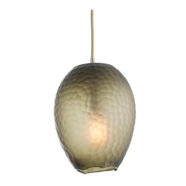 This one-light smokey brown glass pendant features a subtle gradient near the top and bottom of the piece which typically...