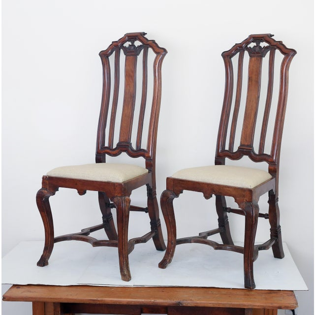 A fine pair of Anglo Dutch chairs in carved walnut with new upholstery and original surface. The carved scroll back joins...