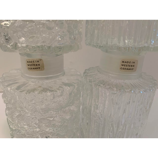A pair of vintage glass decanters - textured brutalist style glass. Marked Made in West Germany. Screw tops with plastic...