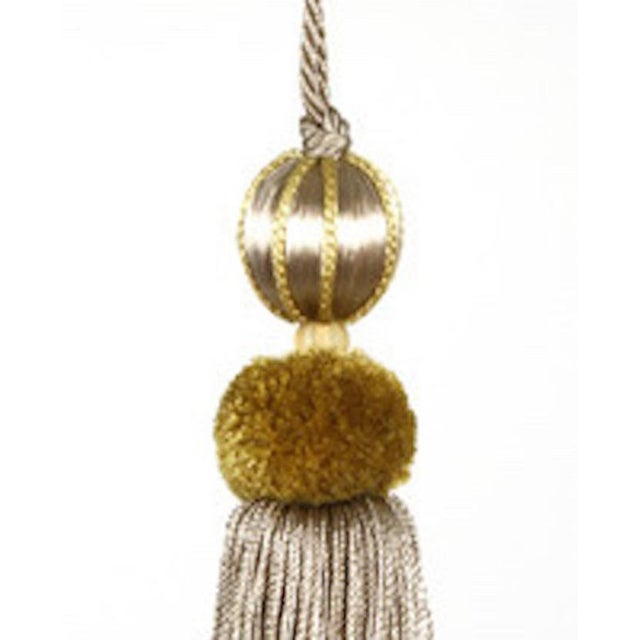Elegant beaded key tassel in shades of gold. This festive tassel is made up of a wooden bead, covered with a soft gold...