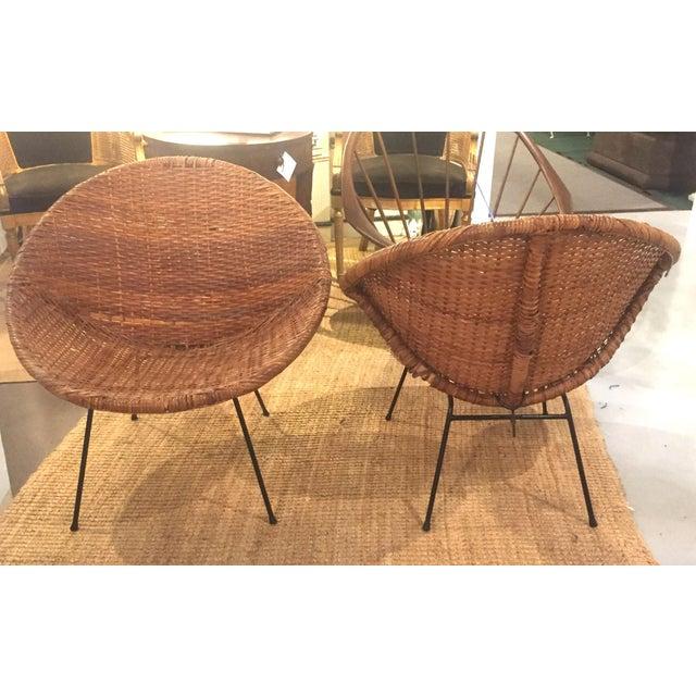 All original pair if mid century rattan, wicker hoop circle chairs. Black metal frame holding original rattan hoop seats....
