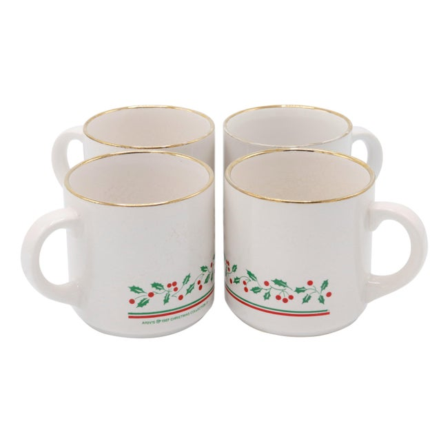 A set of four Christmas cups from Arby's 1987 Christmas Collection. Glazed white ceramic cups trimmed with a gilt lip are...