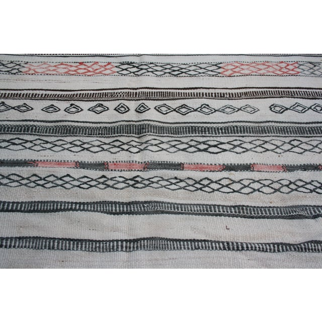 Vintage Moroccan kilim rug handloomed in soft organic wool. Features ornate Berber stripes and symbols of nature.