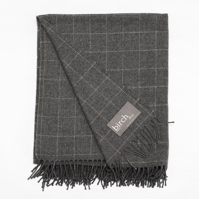 "This Graphite Windowpane Simply Birch Throw is made of 100% lambswool, is 78""L x 57""W and is composed of a graphite color..."