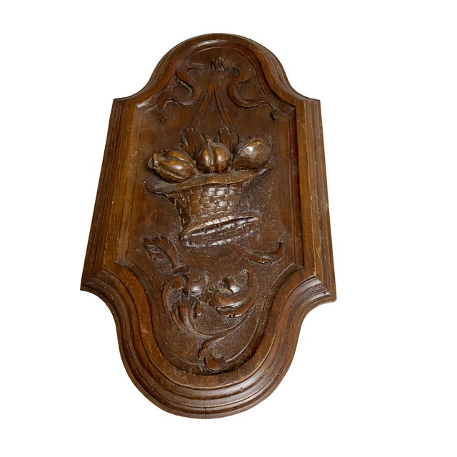 A 19th century English hand carved wooden plaque with a basket of fruit with a bow.