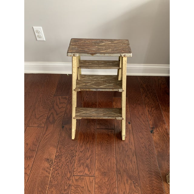 Adorable little step ladder. Sturdy and in usable condition. Great patina - like a cream metal on the legs and metal/rust...