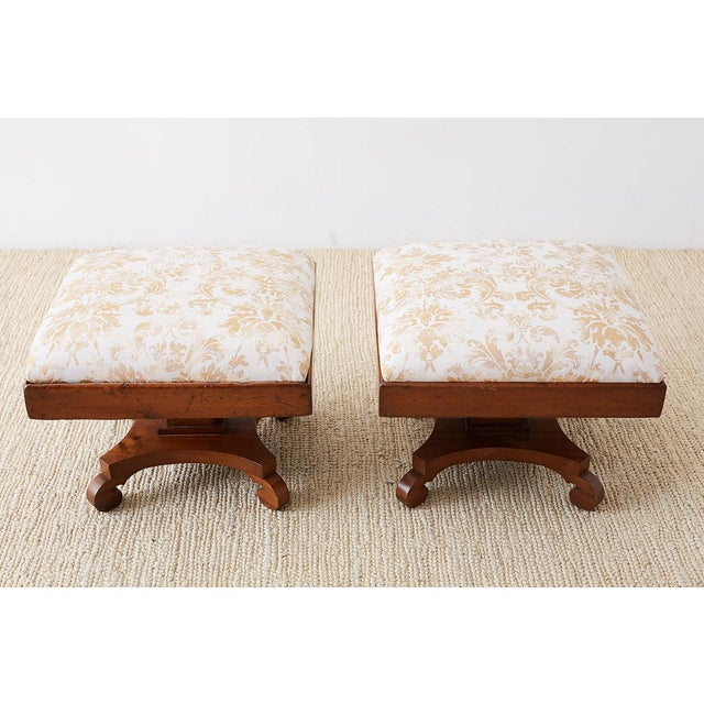 Remarkable pair of hand-carved footstools made in the Biedermeier taste of 19th century Europe. Featuring a Fortuny...