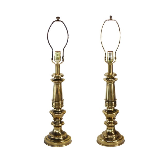 Pair of heavy brass table lamps made by Stiffel. Polished brass with a slightly antiqued finish. Three way switches....