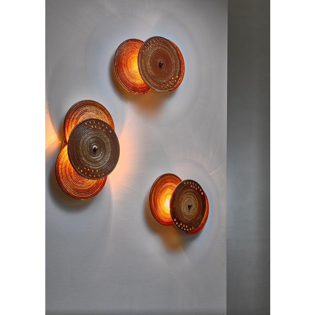 A set of three wall lamps by Axella Stentøj, Denmark. The lamps are made of three earth tone ceramic discs. The disc on...