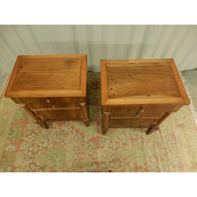 Pair of early 19th century walnut French Empire bedside cabinets with a drawer and door on each. They are not exactly the...