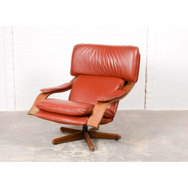 Beautifully designed vintage swivel relax chair from Scandinavian origin with soft maroon leather upholstery and Plywood...