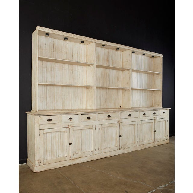 Monumental American kitchen cabinet cupboard or bookcase featuring a rustic painted pine finish. Made in the country...