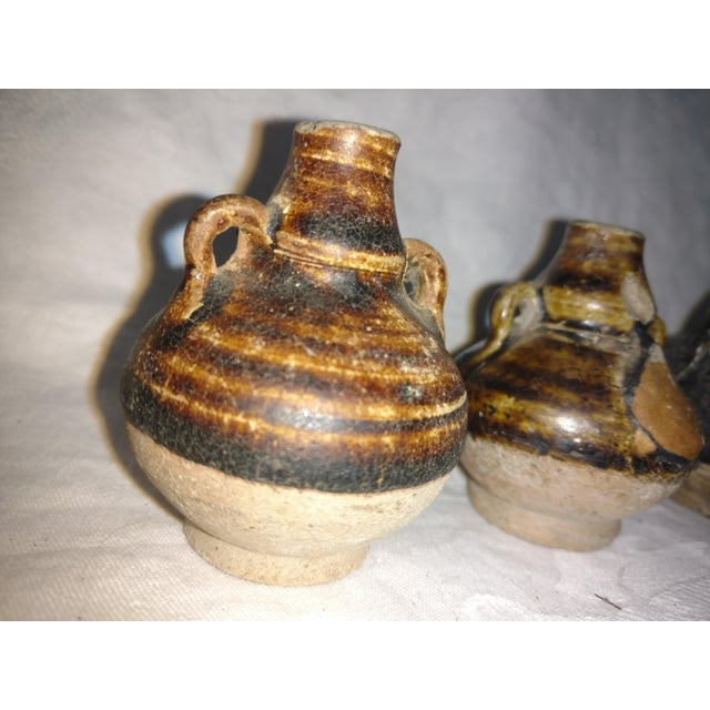 This pottery is called Sukohothai pottery and it is 600 years old from Thailand! These Sukohothai jarlets have a dark...