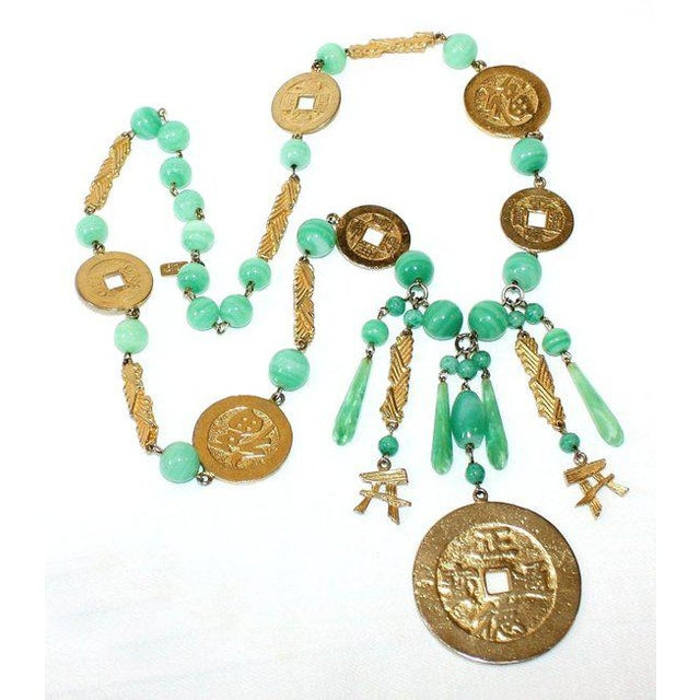 Fabulous looking and compliment getting long necklace made of variegated green glass beads embellished with gold metal...