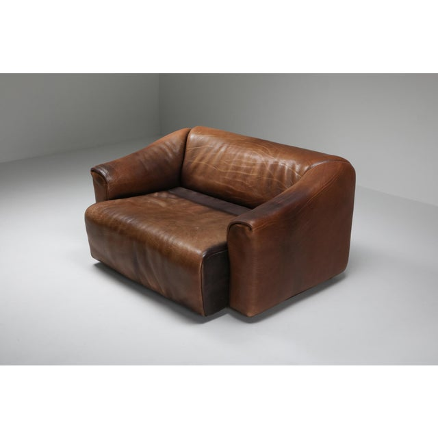 Brown leather two-seat sofa by Swiss manufacturer De Sede. Bullhide leather with retractable seating for an even more...