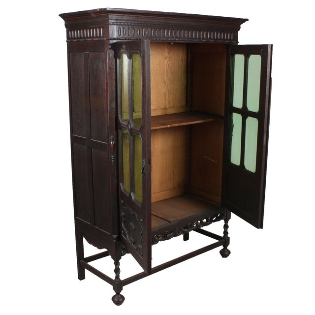 1920s Art Noveau-Jacobean style bookcase constructed of dark stained oak, featuring double doors with green octagon glass...