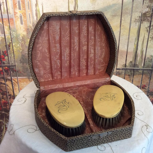 This is a great set of Celluloid Clothing brushes and a dresser box with nice silver tone latch. They are monogrammed with...