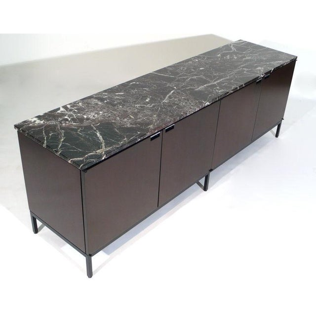 Stunning imported Florence Knoll designed credenza with original Italian marble tops. Four dark mahogany finished doors...